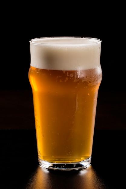 Cerveza en el fondo negro. Foto Premium