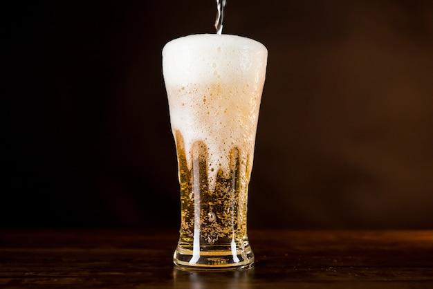 Cerveza fría dorada se vierte en el vaso con espuma espumosa desbordante Foto Premium