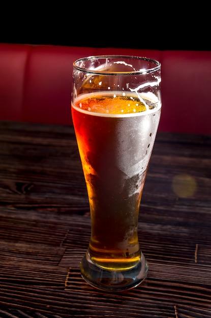 Cerveza light en un vaso sobre una mesa de madera Foto Premium