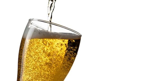Cerveza que vierte en el vidrio aislado en el fondo blanco Foto Premium