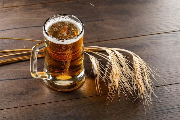 Cerveza en una taza de vidrio con espigas de alto ángulo de visión sobre una mesa de madera Foto gratis