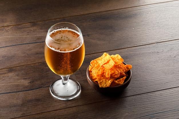 Cerveza en un vaso de copa con chips de alto ángulo de visualización en una mesa de madera Foto gratis