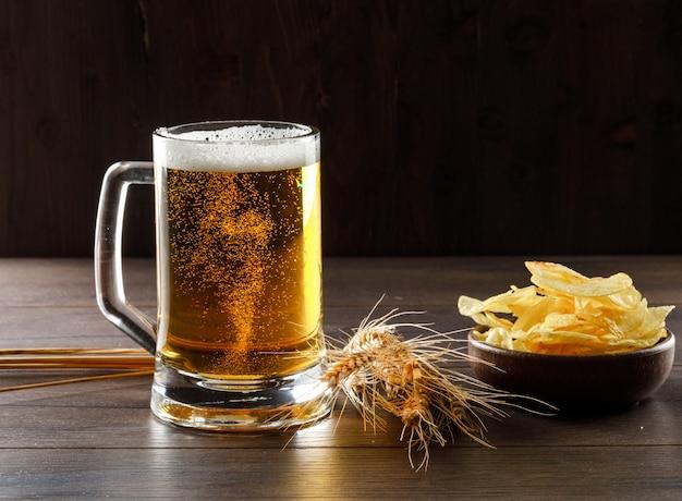 Cerveza en un vaso con espigas, vista lateral de chips en una mesa de madera Foto gratis