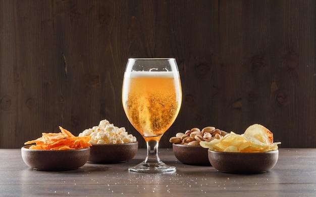 Cerveza en un vaso con vista lateral de comida chatarra en una mesa de madera Foto gratis