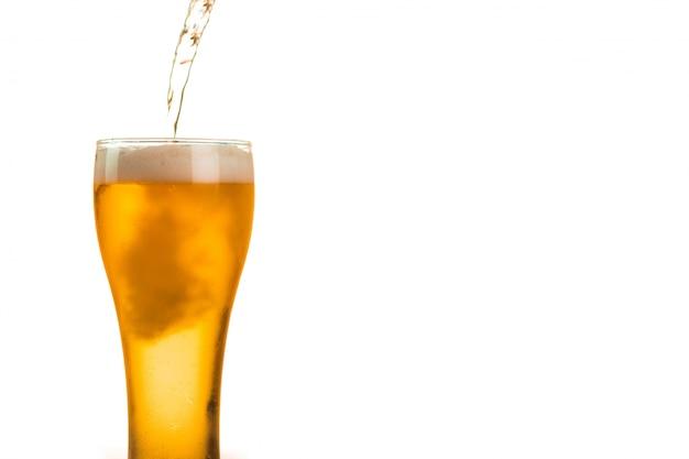 La cerveza se vierte en el vaso Foto Premium