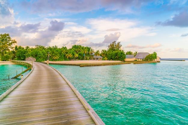Chalets hermosos del agua en la isla tropical de maldivas en el tiempo de la puesta del sol. Foto Premium