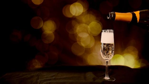 Champagne vertiendo en copa con efecto bokeh Foto gratis