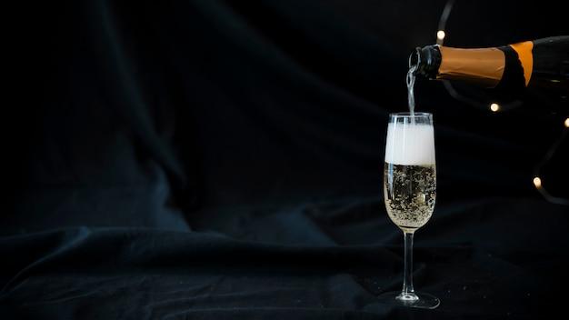 Champagne vertiendo en copa Foto Premium