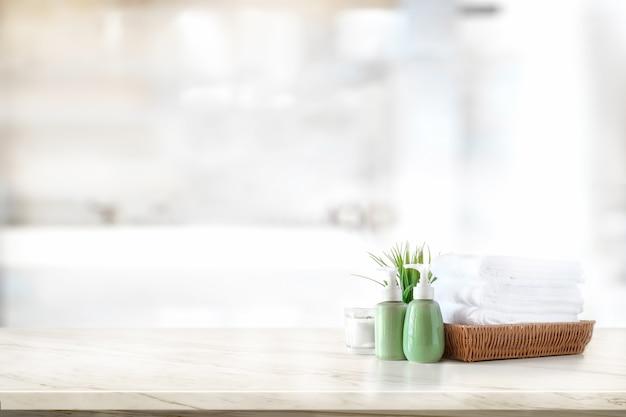 Champú de cerámica, botella de jabón y toallas en mostrador sobre fondo de baño Foto Premium