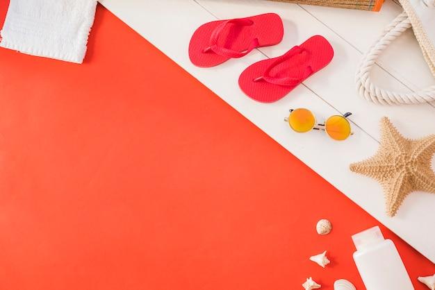 Chanclas cerca de una toalla con estrellas de mar y una botella con gafas de sol entre conchas marinas Foto gratis