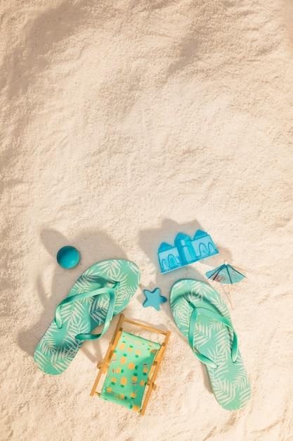 Chanclas y juguetes de arena en la playa Foto gratis