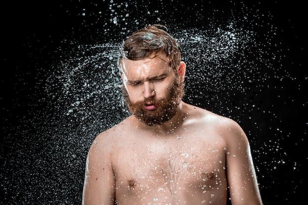 El chapoteo del agua en la cara masculina Foto gratis