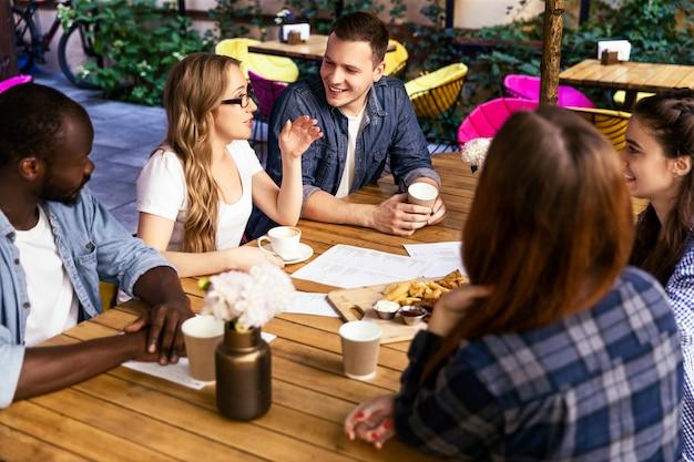 Charla informal con amigos en una reunión semanal en la cafetería local en un caluroso día de verano Foto gratis
