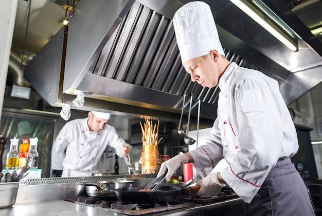 Chef en la cocina del restaurante en la estufa con pan, cocina Foto Premium