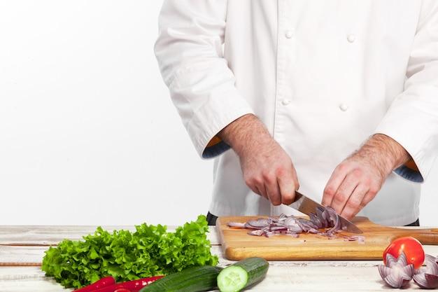 Chef cortando una cebolla en su cocina Foto gratis