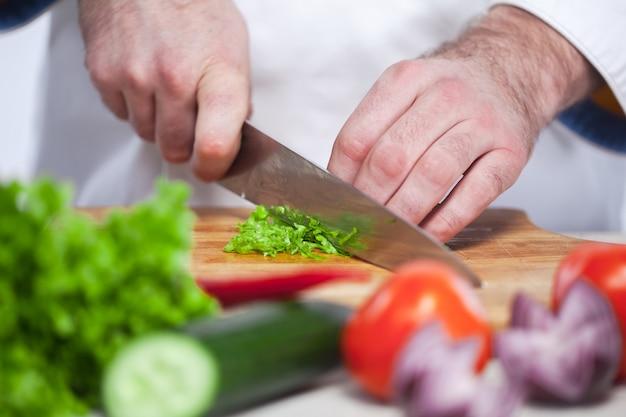 Chef cortando una lechuga verde en su cocina Foto gratis