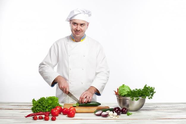 Chef cortando un pepino verde en su cocina Foto gratis