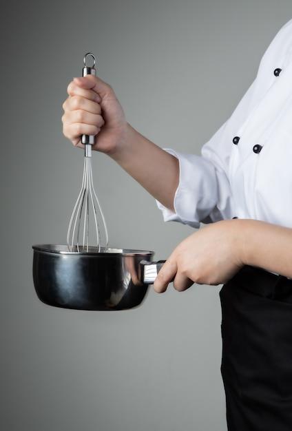 Chef con herramienta para batir ingredientes de mezcla de alimentos de repostería Foto Premium