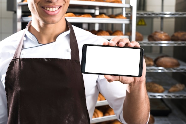Chef mostrando pantalla de telefono Foto gratis