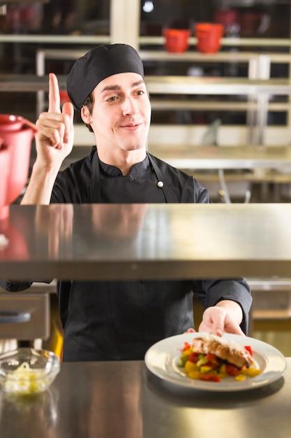 Chef mostrando su plato Foto gratis