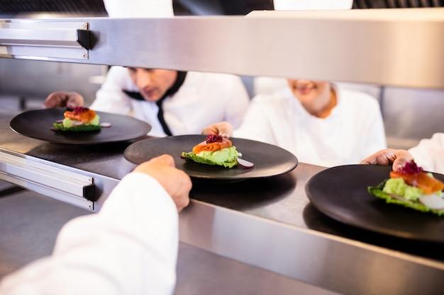 Chef con plato de aperitivo listo en la estación de pedidos Foto Premium
