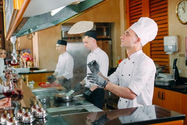 El chef prepara comida frente a los visitantes en el restaurante. Foto Premium