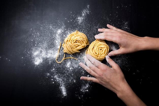 Chef preparando nido de tagliatelle casero italiano en el mostrador de la cocina Foto gratis