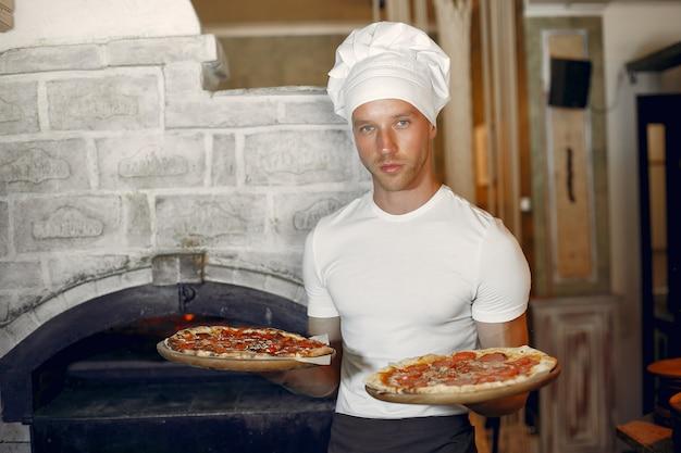 Chef en uniforme blanco prepara una pizzaa Foto gratis