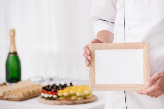 Chef en uniforme con marco de madera con maqueta Foto gratis