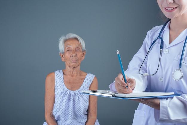 Chequeo de salud del anciano con joven enfermera. Foto gratis