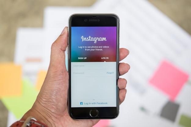Chiang mai, tailandia - 26 de septiembre de 2017: una mano del hombre que sostiene iphone con la pantalla de inicio de sesión de la aplicación del instagram. instagram es la red social de fotografía más grande y popular. Foto Premium