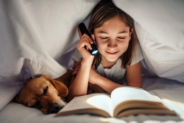 Chica acostada en la cama con su perro debajo de una manta leyendo un libro a altas horas de la noche Foto Premium