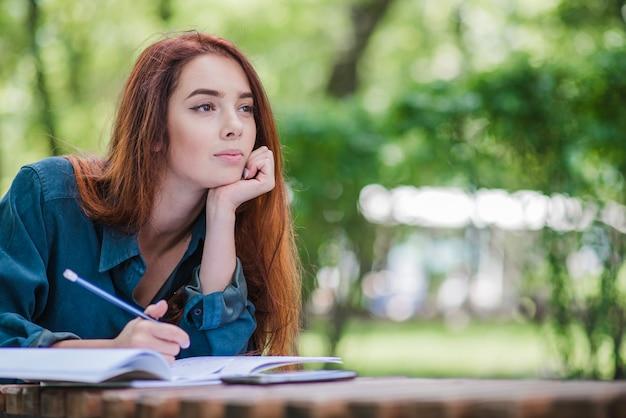 Chica acostado en la mesa en el parque de la escritura Foto gratis