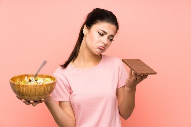 Chica adolescente con ensalada y chocolate y dudas Foto Premium