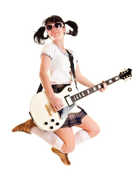 Chica adolescente con una guitarra eléctrica saltando Foto Premium