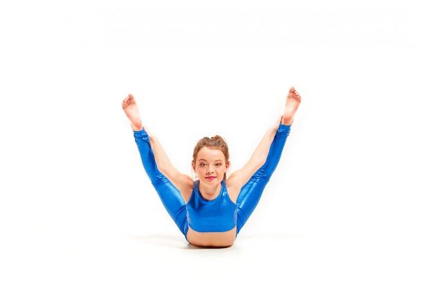 La chica adolescente haciendo ejercicios de gimnasia aislado sobre fondo blanco. Foto gratis