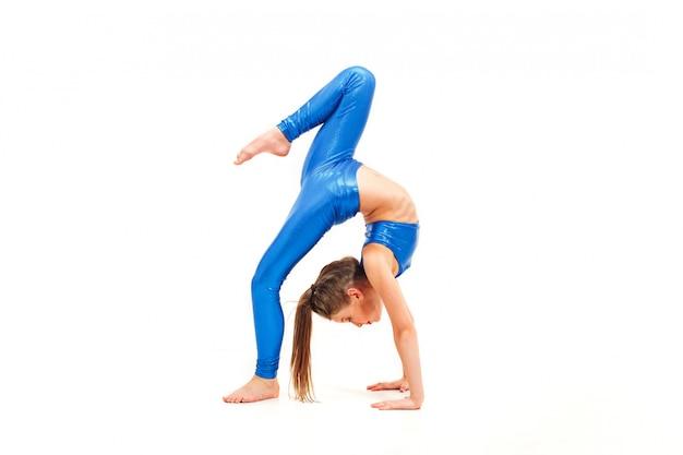 Chica adolescente haciendo ejercicios de gimnasia aislados en blanco Foto gratis