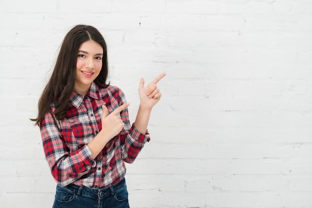 Chica adolescente señalando Foto gratis