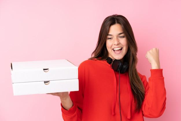 Chica adolescente sosteniendo cajas de pizzas sobre pared aislada Foto Premium