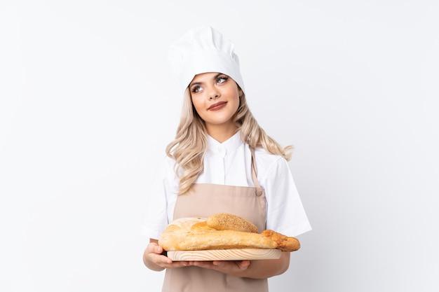 Chica adolescente en uniforme de chef. panadero de sexo femenino que sostiene una tabla con varios panes sobre fondo blanco aislado riendo y mirando hacia arriba Foto Premium