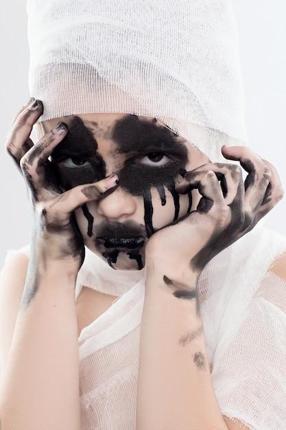 Chica adolescente con vendas de momia en halloween en blanco aislado Foto Premium