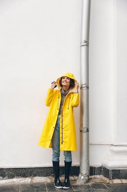 Chica adulta satisfecha 20s vistiendo abrigo amarillo de pie con capucha al mirar hacia arriba disfrutando de clima lluvioso con una sonrisa Foto gratis