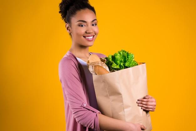 Chica afroamericana con víveres. Foto Premium