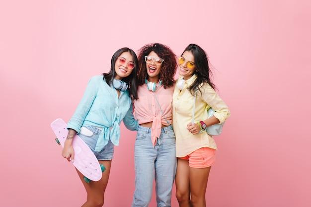 Chica agraciada en camisa amarilla con mochila de cuero posando cerca de amigo rizado africano en jeans. alegre joven negra con gafas de sol de pie entre damas europeas y latinas. Foto gratis
