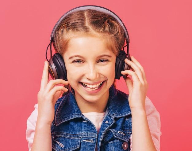 Chica alegre escucha música en auriculares Foto Premium