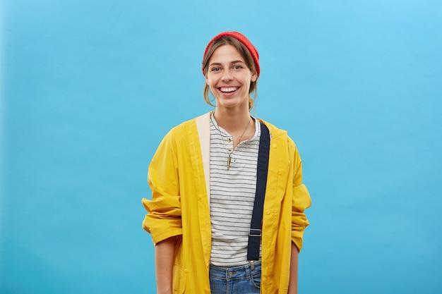 Chica alegre hipster en elegante impermeable amarillo y sombrero rojo Foto gratis