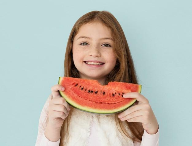 Chica alegre joven sosteniendo una rebanada de sandía Foto gratis