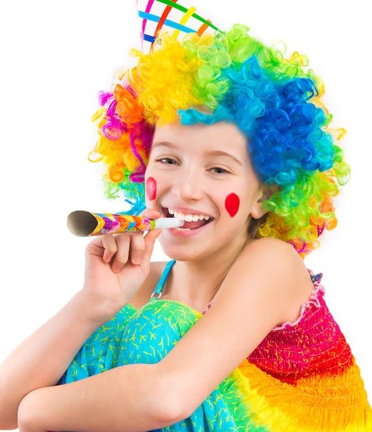 Chica alegre en peluca de payaso rizado y soplador de bocina de fiesta Foto Premium