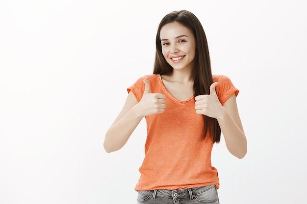 Chica alegre satisfecha, mujer bonita mostrando gesto de aprobación, pulgar hacia arriba, garantía de calidad, como idea Foto gratis