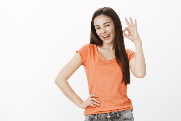 Chica alegre satisfecha, mujer bonita que muestra un gesto de aprobación bien o bien, garantía de calidad, como idea Foto gratis